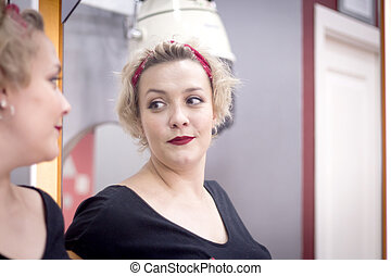 Blonde woman looking in the mirror of a hairdresser