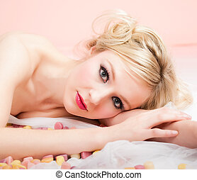 blonde woman lying between sweets
