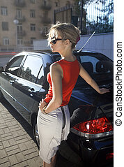 blonde woman near black car
