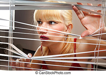 blonde woman observes through blinds
