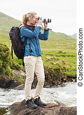 Blonde woman on a hike taking a photo in the countryside