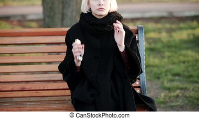 Blonde woman outside Goes into frame sits on a bench Experiences stress a headache Sad dissatisfied