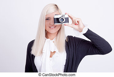 Blonde woman photographing over white background