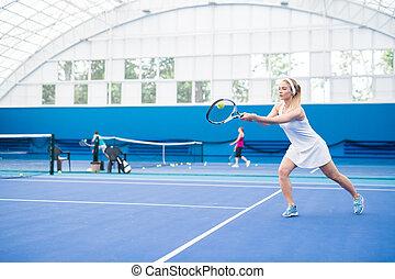 Blonde Woman Playing Tennis Action Shot