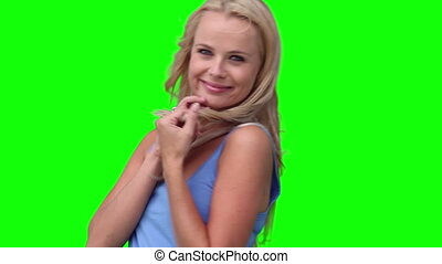 Blonde woman playing with her hair against a green background