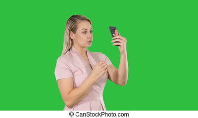Blonde woman preening in front of the smartphone on a Green Screen, Chroma Key.
