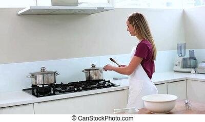 Blonde woman preparing meal in kitc