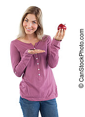 Blonde woman presenting an apple