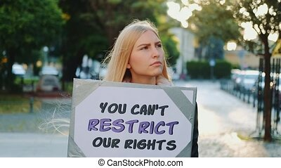 Blonde woman protesting against human rights restriction by walking on the street with placard.