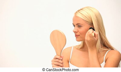 Blonde woman puting on make up with a brush