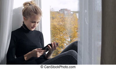 Blonde woman reading a book in e-reader