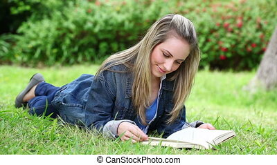 Blonde woman reading a novel in a park