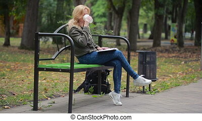 blonde Woman Reading Book on Brench in Autumn Park. drinking hot coffee or tea