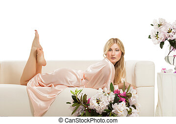 Blonde woman relaxing on her bed