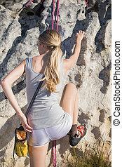 Blonde woman rock climbing