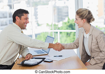 Blonde woman shaking hands while having an interview
