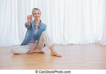 Blonde woman showing new house keys