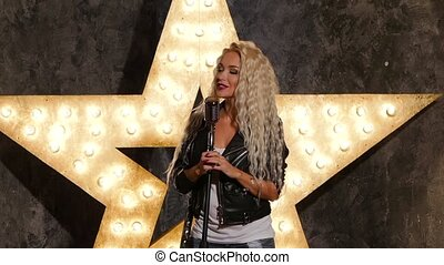 blonde woman singer with microphone, shining star in the background. slow motion