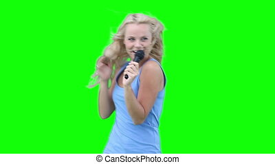 Blonde woman singing into a microphone