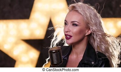 blonde woman Singing  with Retro Microphone, shining star in the background, slow motion, close up