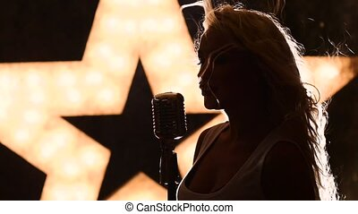 blonde woman Singing with Retro Microphone, slow motion, close up, silhouette