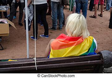 blonde woman sit on bench dressed rainbow gay flag