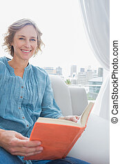Blonde woman sitting on her couch reading a book