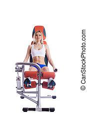 Blonde woman sitting on orange hydraulic exerciser