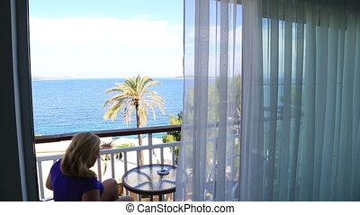 Blonde woman sitting on sea view balcony
