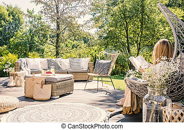 Blonde woman sitting on the terrace of a summer retreat reading a book and relaxing