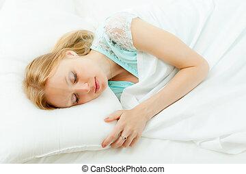 Blonde woman sleeping in  bed