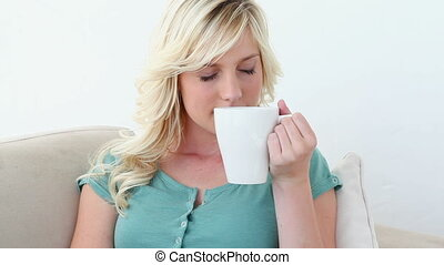 Blonde woman smells and drinks a coffee