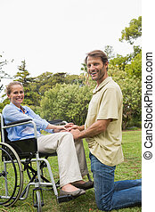 Blonde woman smiling in wheelchair with partner kneeling beside her looking at camera in the park