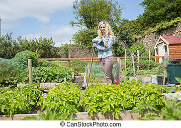 Blonde woman standing in her garden