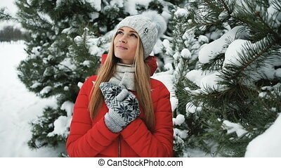Blonde woman standing in winter frosty landscape near fir trees. Beautiful Russian female with fair hair, blue eyes enjoying nature, snowy, cold weather in coniferous forest. Cute romantic lady in warm clothes, red jacket, knitted sweater hat mittens stands, observes, looks into distance in pine ...
