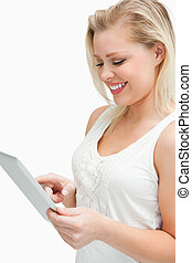 Blonde woman standing while using her tablet computer