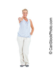 Blonde woman standing with thumbs up smiling at camera