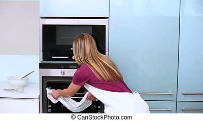Blonde woman taking cookies in oven