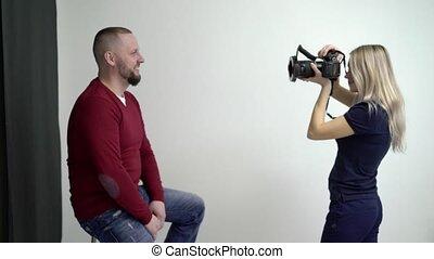 Blonde woman taking photo in studio of man