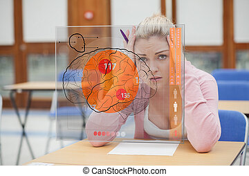 Blonde woman thinking hard while studying on interface with brain on it