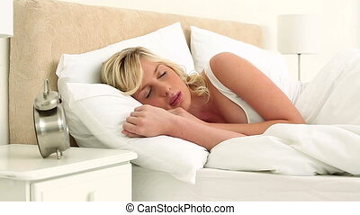 Blonde woman throwing her alarm clock away