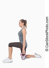 Blonde woman training with kettle bell while lunging on...
