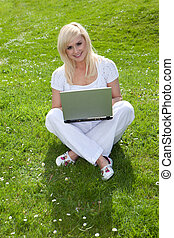 Blonde woman using a laptop on the grass