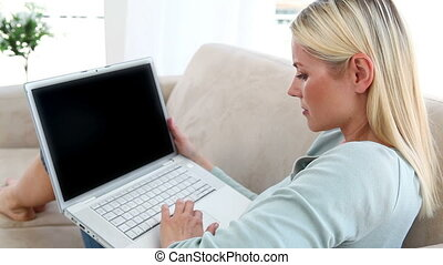 Blonde woman using a laptop