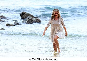 Blonde Woman walking through the water