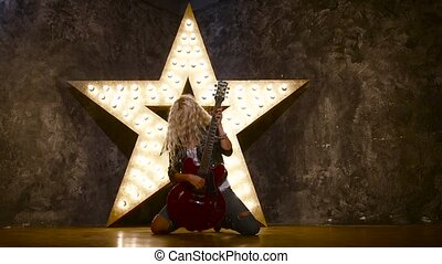 blonde woman wearing leather jacket and playing a guitar,...