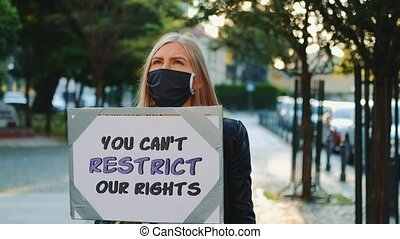 Blonde woman wearing medical mask protesting against human rights restriction by walking on the street with placard.