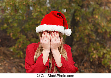 Blonde woman with Christmas hat covering her face