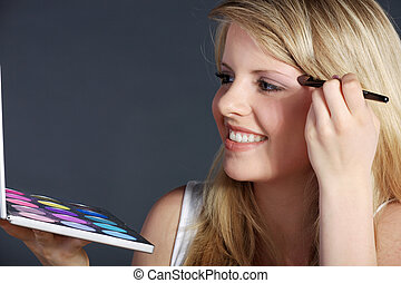 blonde woman with cosmetics brush