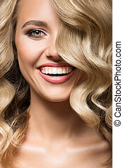 Blonde woman with curly beautiful hair smiling. Close up portrait.